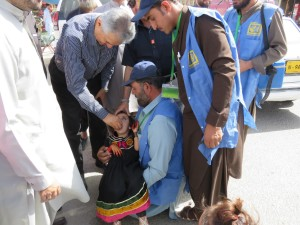 2  National Chair Aziz Memon giving polio drop to a child in transit (2)