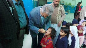 NPPC Chair Aziz Memon administrating polio drops to the child